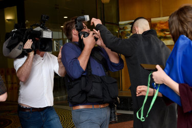 Menouar Belkadi pushes past photographers as he arrives at the Downing Centre Court in Sydney on Friday.