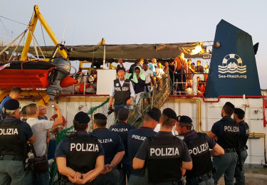 Migrants disembark from the Dutch-flagged Sea-Watch 3 ship.