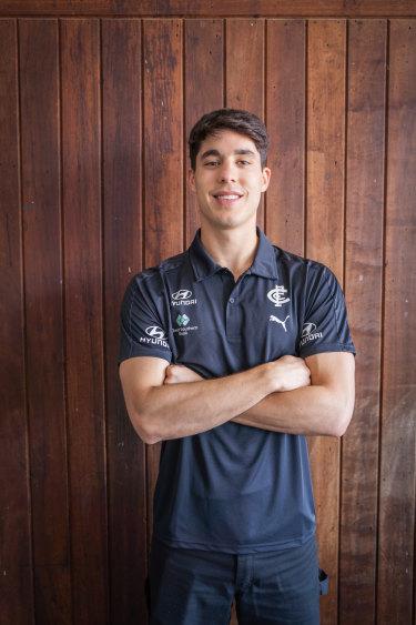 New Carlton midfielder Adam Cerra puts on his navy blue polo after Thursday's trade.