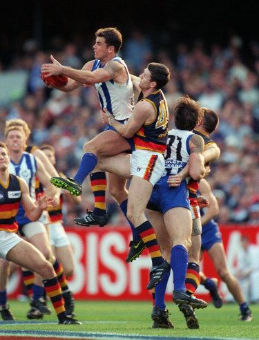 Memorable mark: Peter Caven fails to spoil Wayne Carey's mark in the 1998 grand final.