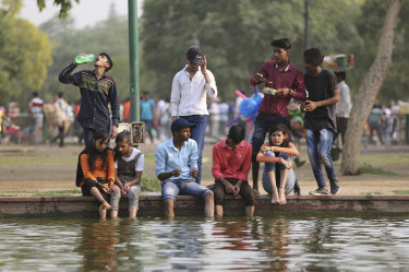 Indians sit on the edge of a pond near the India Gate monument on a hot day in New Delhi when the mercury climbed to 45 degrees in May 2018.
