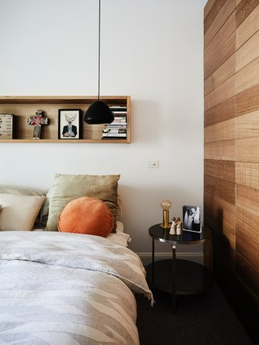 In the master bedroom, a new wall was built in Tasmanian oak, in keeping with the aesthetic of the home's addition. The black pendant light is by Melbourne designer Ross Gardam.