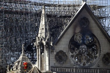 A fire fighter makes his way on a balcony of Notre-Dame cathedral following the blaze.