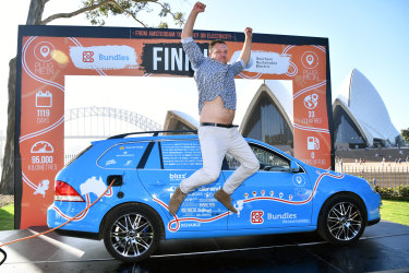 Dutchman Wiebe Wakker celebrates after arriving in an electric vehicle at the Royal Botanic Gardens in Sydney on Sunday.