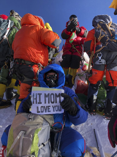 US doctor Ed Dohring holds up a sign for his mother, as climbers jockey for space on the summit of Mount Everest.