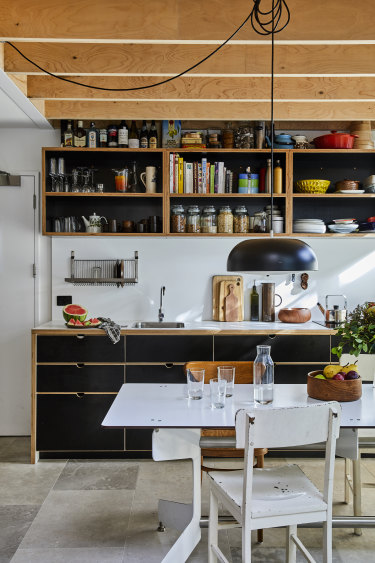 Space was saved in the kitchen by not having a dishwasher or range hood and by using double drawers. An induction cooktop also doubles as bench space.