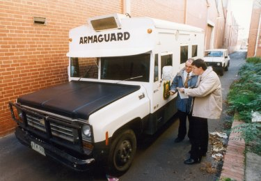 Police examine the abandoned Armaguard van after the 1994 armed robbery in Richmond.