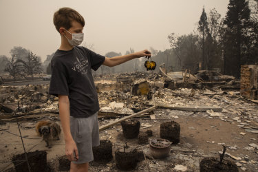 Jacen Sullivan, 14, from Talent, Oregon, holds a burned tomato he found in the garden at his burned home.