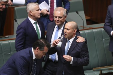 Treasurer Josh Frydenberg is congratulated by Prime Minister Scott Morrison and other colleagues after delivering the budget.