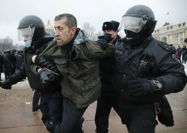 Police detain a man during a protest against the jailing of opposition leader Alexei Navalny.
