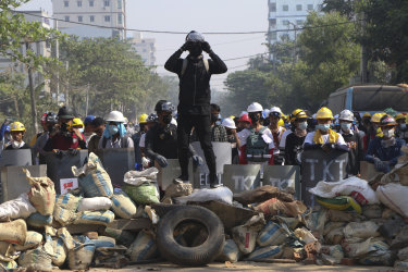 Protesters take positions behind a barricade as police gather in Yangon in March.
