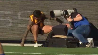 Hawthorn's Chad Wingard collides with photographer after kicking a beauty of a goal.