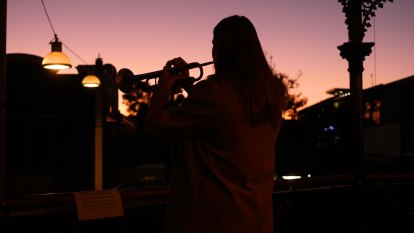 Sarah Brown plays The Last Post from the balcony of The Royal in Leichhardt