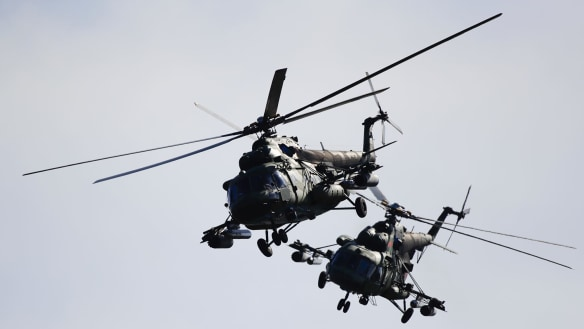 Two Belarusian military helicopters fly during military exercises, near the Volka village, 200 kilometers south-west of Minsk, Belarus.