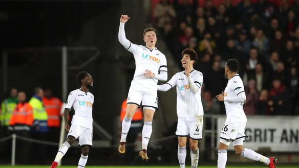 Giant leap towards safety: Alfie Mawson celebrates after scoring for Swansea.