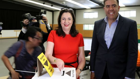 Queensland Premier Annastacia Palaszczuk, joined by the Federal Member for Oxley Milton Dick, casts her vote in the state's election at Inala State School in Brisbane.