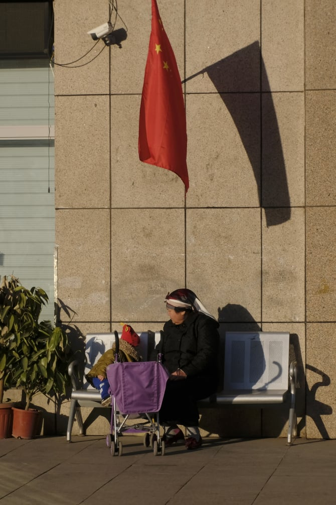 A Uighur woman and a child sit under China's national flag and a CCTV camera in Urumqi,  Xinjiang.