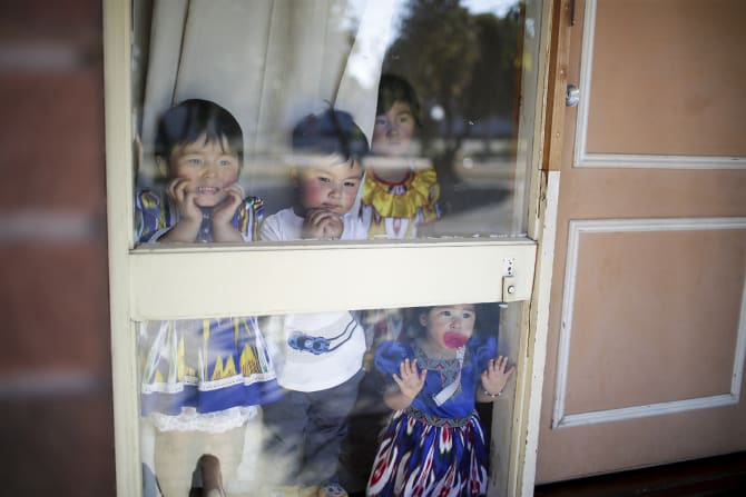Uighur children Efruz, Abdukuddus, Elif and Melek watch as a car pulls into their driveway at their home in Adelaide.