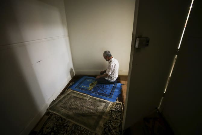 Abdulwali Muhammad during evening prayers in a prayer room while dining at a Uighur restaurant that used to be a church.