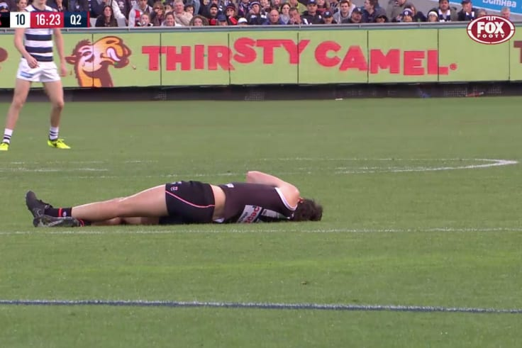 Roberton lies on the ground after collapsing.