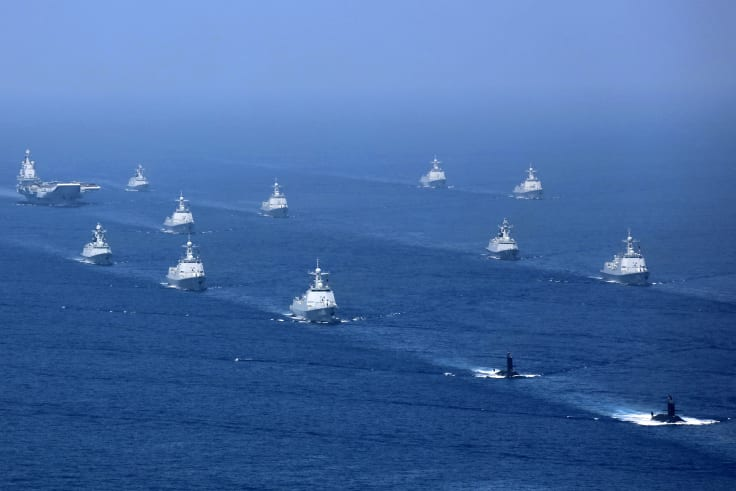 Chinas's Liaoning aircraft carrier is accompanied by navy frigates and submarines conducting exercises in the South China Sea.