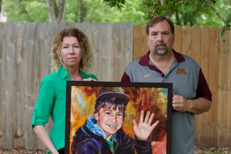 Melissa and Jim Crowley hold painted portrait of their son Alex Crowley, a Tartan student lost to brain cancer in 2012.