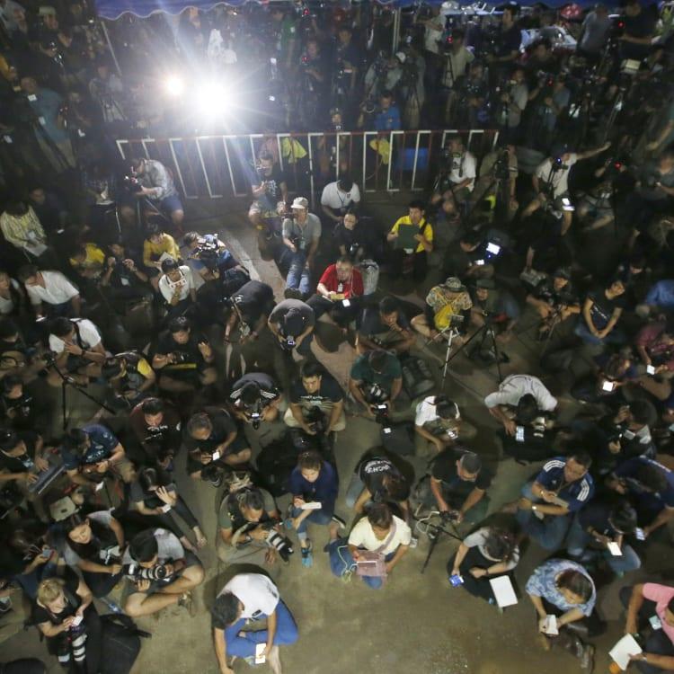 Thai media listen as Province Acting Governor Narongsak Osatanakorn speaks at a press conference.