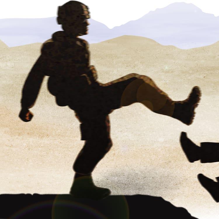 A special forces soldier kicks an Afghan prisoner.