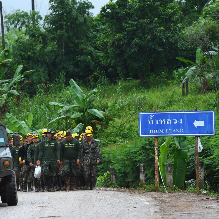Thai army soldiers return from the base camp near Tham Luang cave.