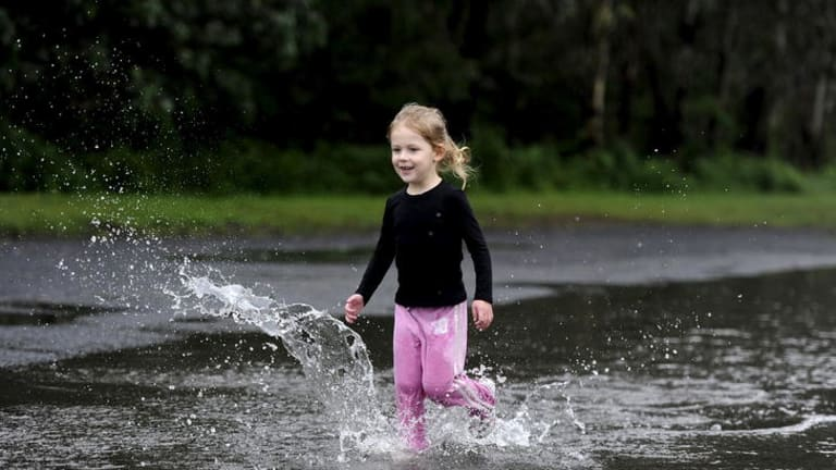 A girl runs through a puddle in the Sydney suburb of Penrith.