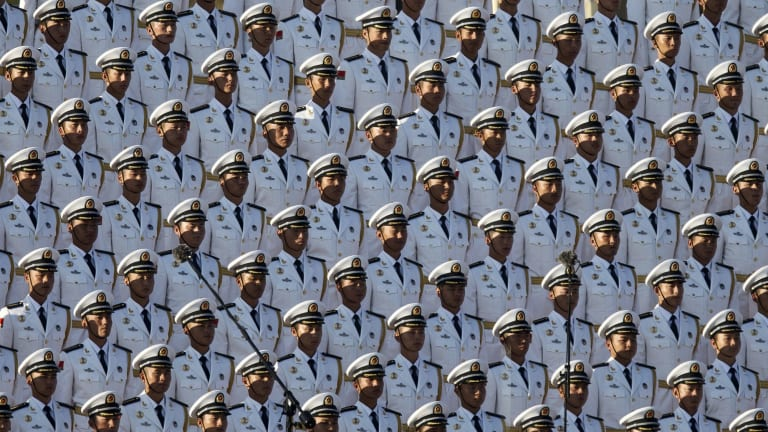 Chinese soldiers stand at attention before the parade: Xi's government is struggling to balance its pledge to loosen its grip on the economy with the desire to ensure stability and maintain confidence in the Communist Party.