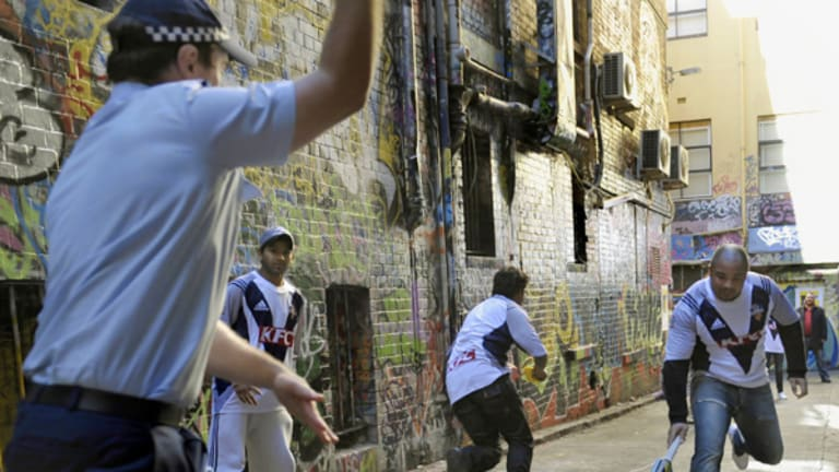 Police and Indian students play a game of laneway cricket in the CBD yesterday.