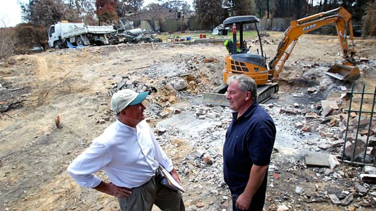 Family team: Builder Philip Bartush (left) consults his brother Dave about plans for a fire-resistant house to replace the one that was destroyed.