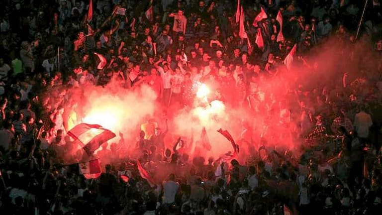 Protesters light flares in Cairo.