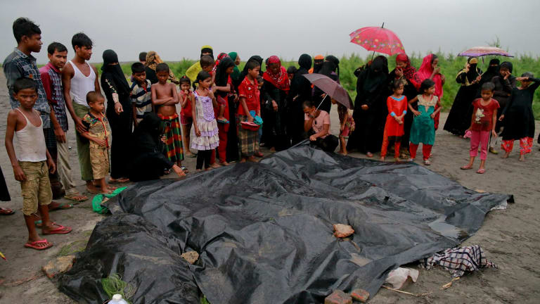 Bangladeshi villagers gather around the covered bodies of Rohingya women and children who died after their boat capsized.