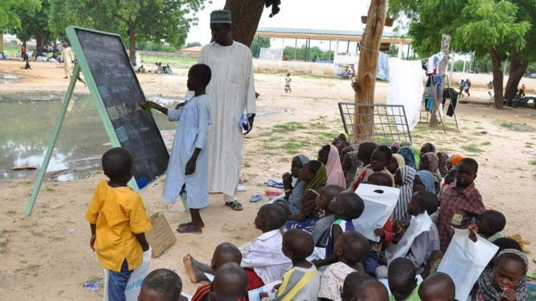 Children who fled their homes following an attack by Islamist militants in Bama, take a lesson at a camp in Maiduguri, Nigeria.