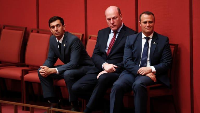 Liberal MPs Trevor Evans, Trent Zimmerman and Tim Wilson listen to Senator Dean Smith speak during debate on the Marriage Amendment bill in the Senate in Canberra.