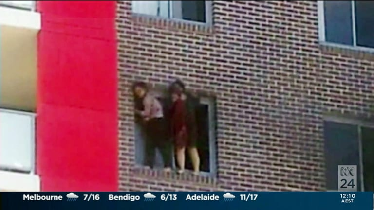 "Yinou ""Ginger"" Jiang and Pingkang ""Connie"" Zhang cling to the side of their apartment building before being forced to jump."