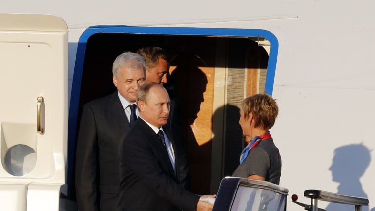 Russian President Vladimir Putin, foreground left, shakes hands with an aircrew member upon his arrival at the Beijing Capital International Airport in Beijing on Wednesday.