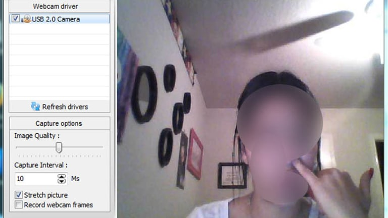 An image uploaded to a hacking forum showing a woman picking her nose as seen through her webcam.