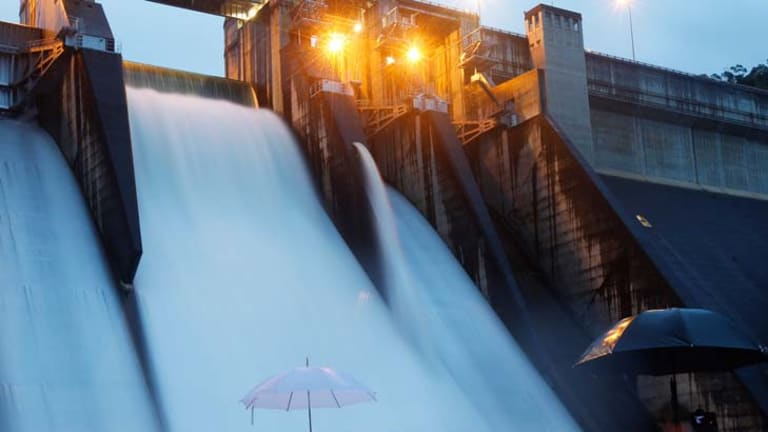 Going with the flow … Warragamba Dam spills over for the first time in 14 years, providing quite a spectacle for a small crowd of police, water catchment staff and sightseers.