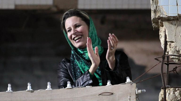 Seeking refuge ...  Muammar Gaddafi's daughter Aisha supports a pro-government rally last month. She has reportedly fled to Tunisia with her mother.