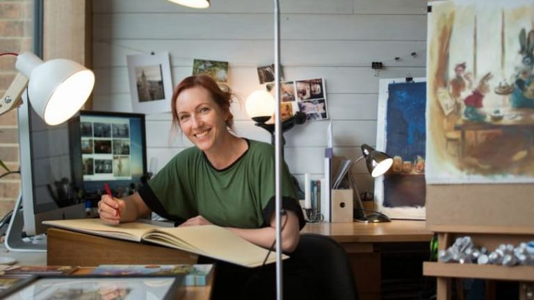 Elise Hurst  in her studio with her work.