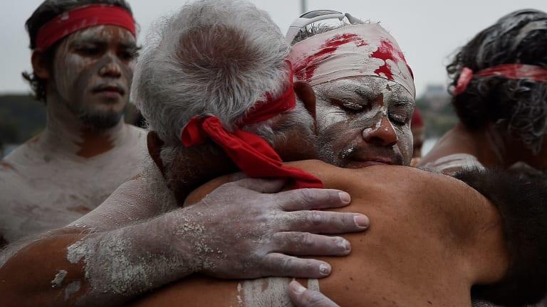 Members of the Koomurri Aboriginal Dance Troup embrace.