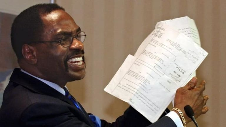 "Rubin ""Hurricane"" Carter holds up the writ of habeas corpus that freed him from prison, during a news conference in California in 2004."