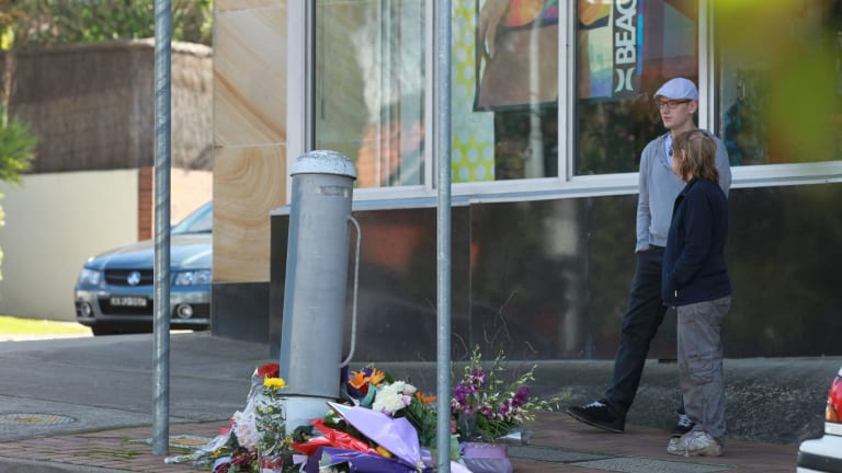 Flowers left for a pedestrian killed after being hit by a bus at an intersection in Beecroft.