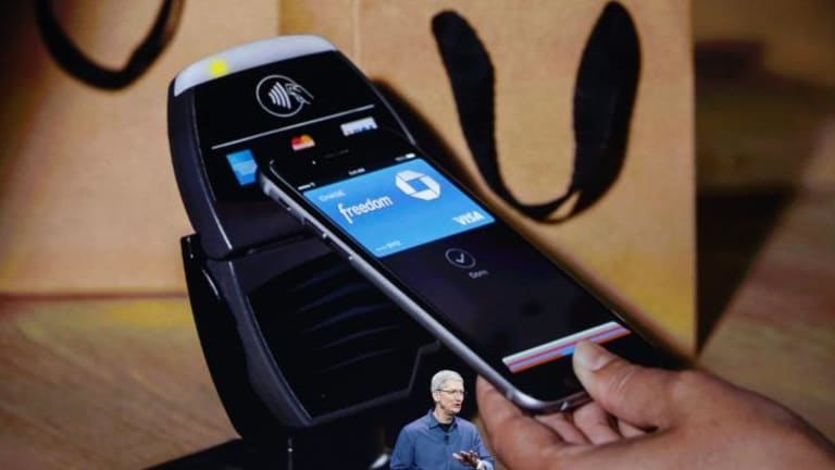 An Apple iPhone making a tap and go transaction behind CEO Tim Cook.