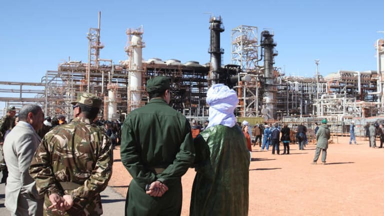 Algerian soldiers and officials stand in front of the gas plant in Ain Amenas, seen in background, during a visit organized by the Algerian authorities following the January 2013 attack directed by Moktar Belmoktar.