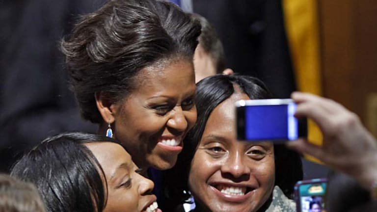 Michelle Obama is all smiles as she poses with US Army sergeants Keisha Whitmore (left) and Tyeir Pritchard-Davis this week.
