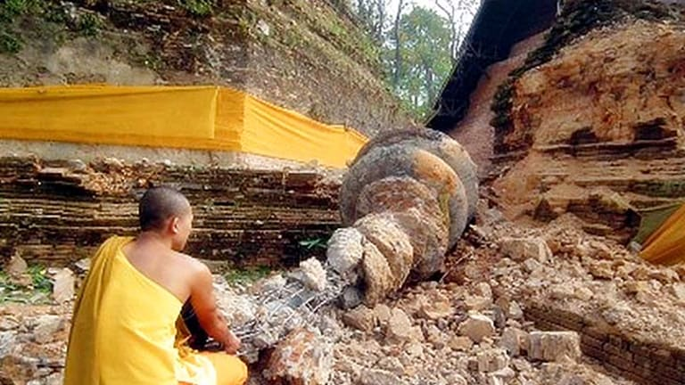 A Thai Buddhist monk inspects a shrine destroyed in the quake